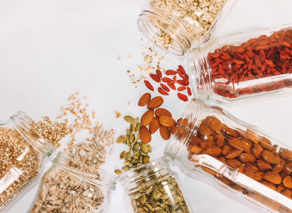 spilled jars of seeds, nuts, and goji berries
